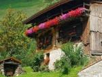 Antigua casa con flores en el balcón