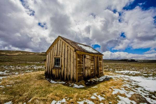 Cabaña de madera y restos de nieve