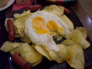 Huevos estrellados con chips y trozos de chistorra