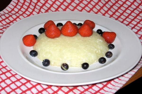 Un budín de queso, decorado con fresas y arándanos