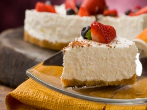 Porción de cheesecake con fresas y arándanos