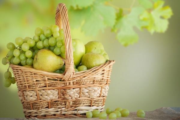 Cesta con peras y uvas blancas