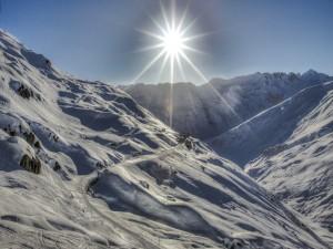 Postal: Los rayos del sol, sobre las montañas nevadas