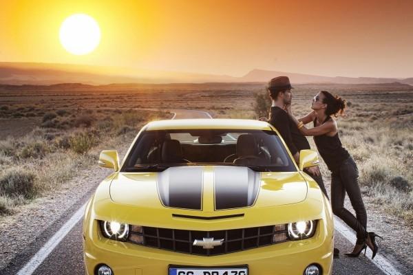 Pareja junto a un Chevrolet Camaro amarillo