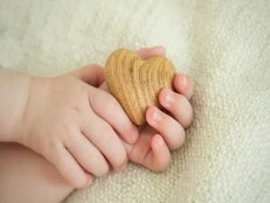 Postal: Manos de bebé sosteniendo un corazón