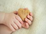 Manos de bebé sosteniendo un corazón
