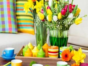 Colorido arreglo con flores, velas y tazas