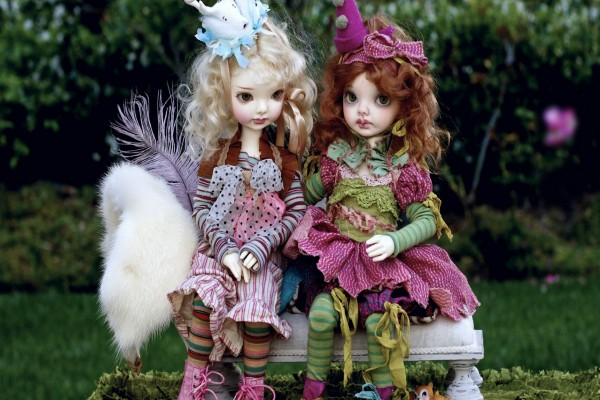 Dos bellas muñecas sentadas en un banco