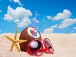 Gafas de sol, coco y estrella sobre la arena