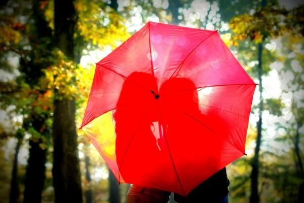 Pareja de enamorados, detrás de un paraguas rojo