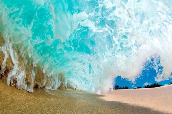 Gran ola rompiendo sobre la arena de la playa