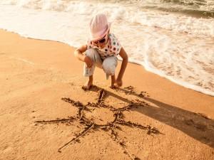 Postal: Dibujando el sol en la arena