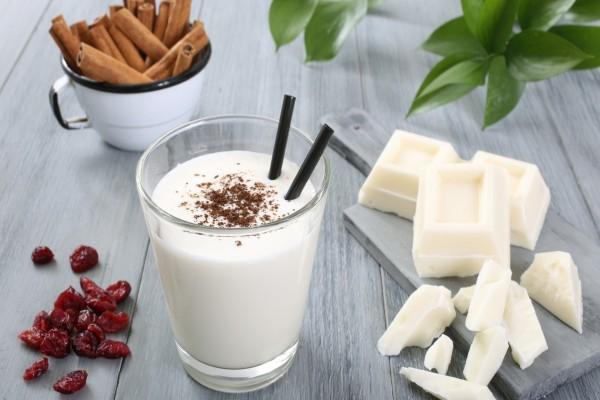 Vaso con yogur, acompañado con chocolate blanco, arándanos secos y canela