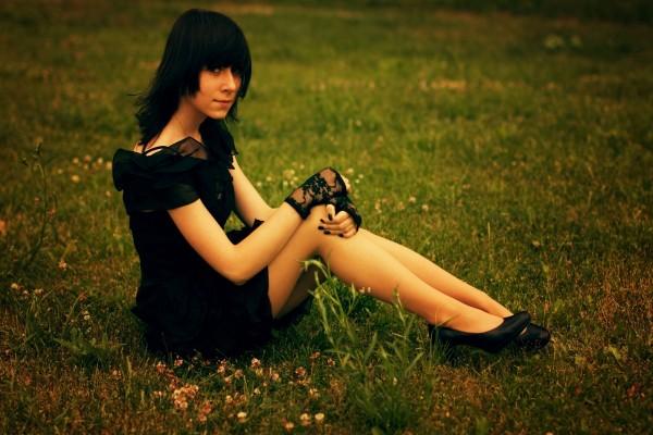 Chica vestida de negro, sentada en la hierba