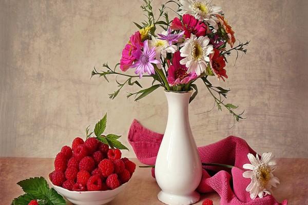 Jarrón con flores y un plato con frambuesas