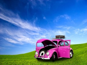 Postal: Coche color rosa, bajo un cielo azul
