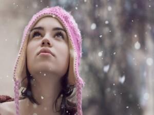 Una joven mirando la nieve caer
