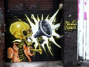 Postal: Esqueleto con un megáfono, pintado en la pared