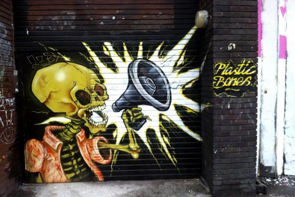Esqueleto con un megáfono, pintado en la pared