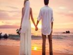 Pareja de recién casados, admirando la puesta del sol en el mar