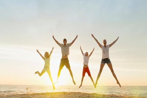 Familia saltando de felicidad en la playa