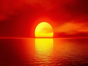 El sol sobre el agua en un cielo rojizo