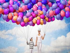 Madre e hijo llevando globos de varios colores
