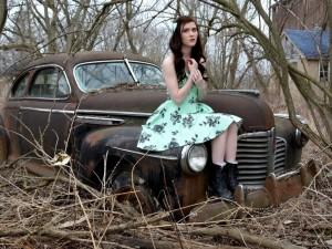 Mujer sentada en un auto abandonado