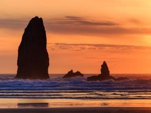 Preciosa playa con grandes rocas y un cielo naranja