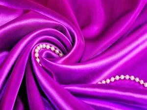 Postal: Collar de perlas sobre una sábana morada