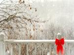 Valla de madera con nieve y un lazo rojo