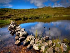 Postal: Camino de piedras atravesando el río