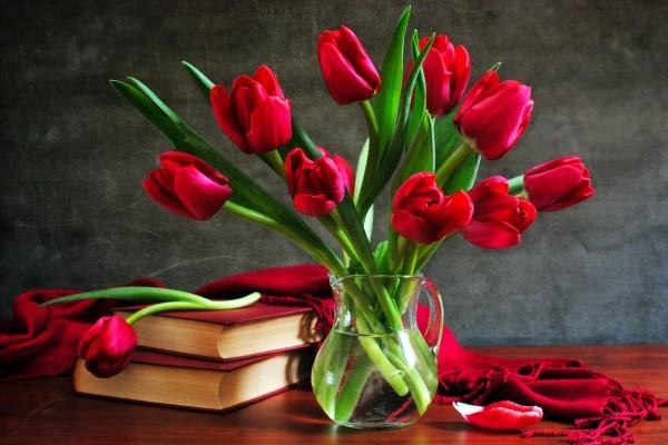Jarrón con tulipanes junto a unos libros