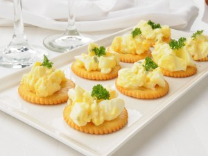Huevos revueltos sobre galletitas saladas