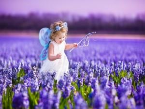 Nena caminando por un campo con flores