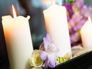 Velas blancas encendidas y un ramito de flores