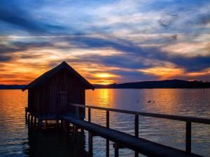 El ocaso del sol sobre el agua y una casita