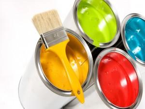 Latas con pintura de colores y una brocha