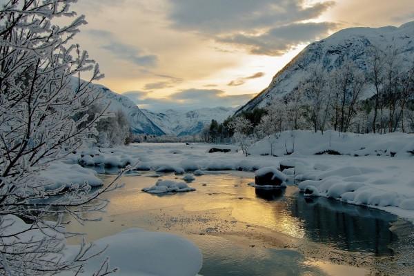 Río bajo la nieve y montañas