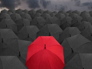 Un paraguas rojo entre negros