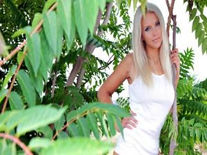 Postal: Atractiva modelo rubia entre los árboles
