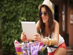Postal: Mujer mirando la tablet sobre la bicicleta