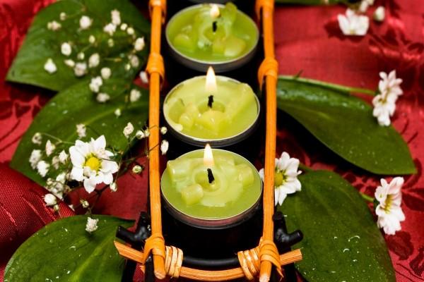 Decoración con velas encendidas, flores y hojas verdes