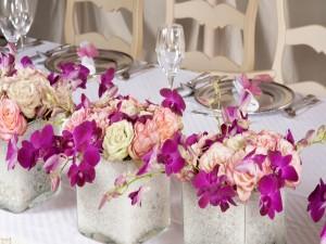 Flores en recipientes de vidrio adornando la mesa