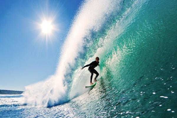 El brillo del sol sobre el surfista en la gran ola