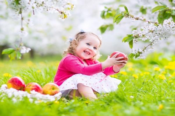 Alegre nena junto a unas manzanas