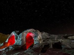 Postal: Rocas iluminadas en una noche estrellada