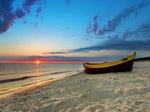 Una  barca en la arena de la playa al atardecer