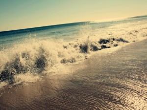 El agua del mar mojando la arena de la playa