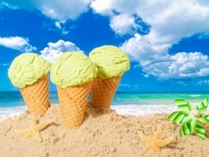 Tres conos con helado en la arena